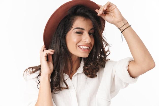 帽子をかぶってポーズをとって、白い壁の上に孤立して立っているカジュアルな服を着て美しい陽気な若いブルネットの女性
