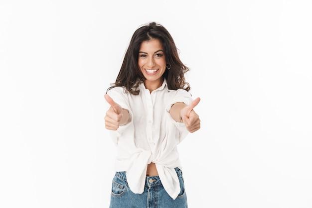 白い壁の上に孤立して立っているカジュアルな服を着て、親指を見せて美しい陽気な若いブルネットの女性