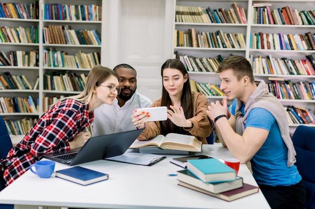 Красивая жизнерадостная молодая кавказская девушка студента показывая информацию на ее smartphone к ее радостным многонациональным друзьям во время их подготовки команды к экзаменам в библиотеке