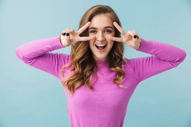 Красивая веселая молодая девушка в повседневной одежде стоит изолированно над синей стеной, показывая жест мира