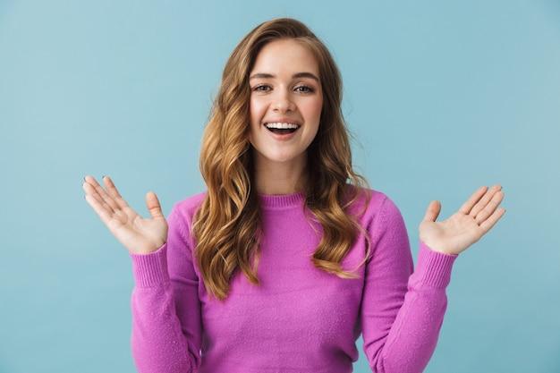 Красивая веселая молодая девушка в повседневной одежде, стоящая изолированно над синей стеной