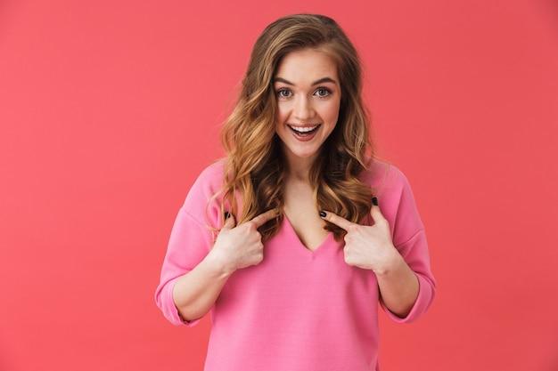 Красивая веселая молодая девушка в повседневной одежде стоит изолированно над розовой стеной, указывая пальцами на себя