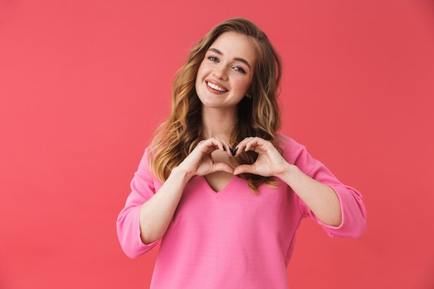 Красивая веселая молодая девушка в повседневной одежде стоит изолированно над розовой стеной, показывая жест сердца