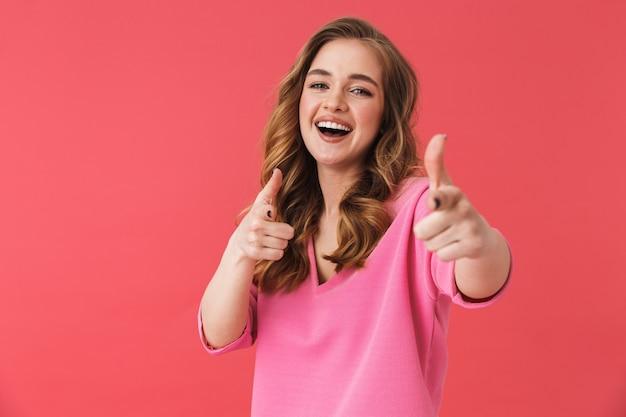 Красивая веселая молодая девушка в повседневной одежде, стоящая изолированно над розовой стеной