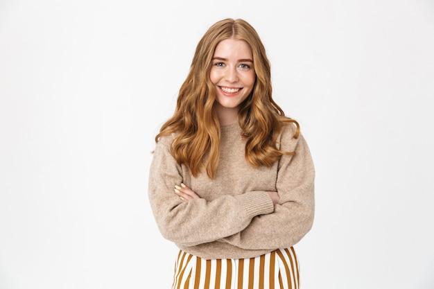 긴 금발 곱슬 머리에 스웨터를 입고 흰 벽에 고립 된 채 팔짱을 끼고 서있는 아름다운 쾌활한 소녀