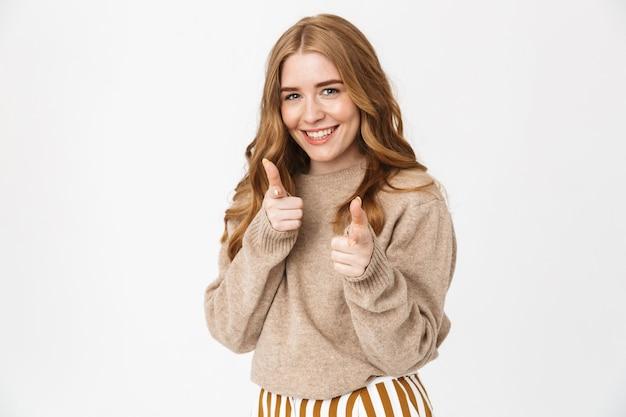 긴 금발 곱슬 머리에 스웨터를 입고 흰 벽에 고립 된 채 손가락을 가리키는 아름다운 쾌활한 어린 소녀