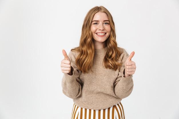 긴 금발 곱슬머리에 스웨터를 입은 아름다운 쾌활한 어린 소녀가 흰 벽에 고립되어 서서 엄지손가락을 치켜들고 있다