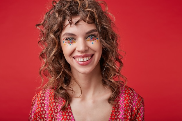 Beautiful cheerful young lady with curly hair and festive makeup standing in motley patterned top, looking with happy wide smile