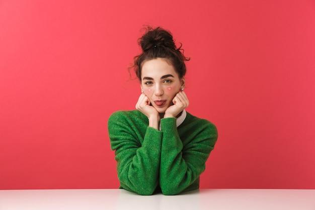 孤立したテーブルに座っている美しい陽気な若い学生の女の子