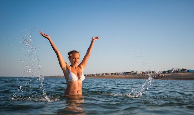 아름 다운 쾌활 한 젊은 여자는 물에 목욕 하 고 햇살 따뜻한 여름 저녁에 그녀의 손을 들어 기뻐