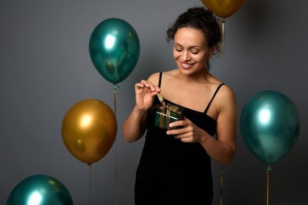 저녁 발크 드레스를 입은 아름답고 쾌활한 젊은 여성은 손에 선물을 들고 광고를 위한 복사 공간이 있는 회색 배경에 부풀려진 다채로운 녹색 금속 및 황금색 공기 풍선에 대해 포즈를 취한 미소를 지었습니다.