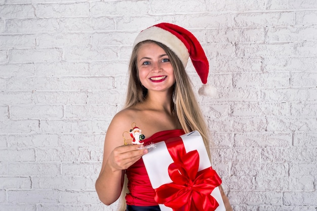 大きな赤い贈り物やプレゼントを保持している赤いドレスの美しい陽気な若い女性