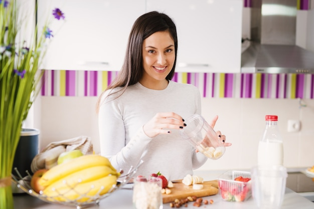 Красивая веселая молодая женщина наполняет чашку шейкер со свежими кусочками фруктов.