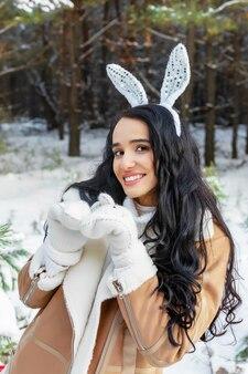 冬の森で彼女の頭にバニーの耳を持つ美しい陽気な若い女性