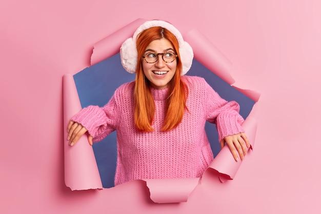 Bella giovane donna allegra con i capelli rossi indossa occhiali e paraorecchie caldi.