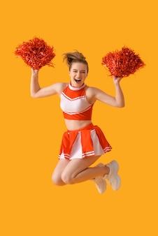 Beautiful cheerleader on color surface