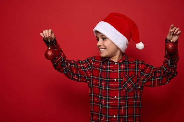 Красивый ребенок мальчик в клетчатой рубашке и шляпе санта-клауса, глядя на елочные игрушки в его руках, изолированные на красном фоне с копией пространства для рекламы