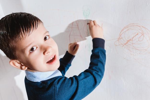 美しい子供は色鉛筆で壁に描きます