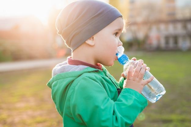 Красивый ребенок пьет воду из бутылки в жаркий летний день