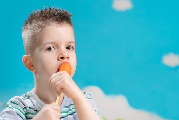美しい子供は棒で新鮮なニンジンを食べます。少年は青い背景に野菜をかじります。