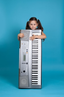 Beautiful child embracing an upright electronic synthesizer and hiding behind it