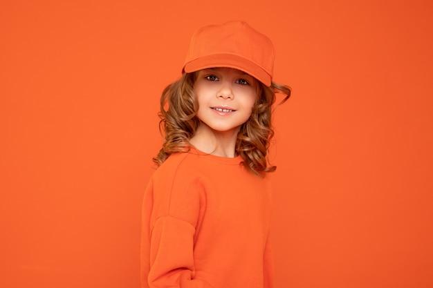 Красивая девочка 6-7 лет в оранжевой кепке с местом для текста, макет. студийная съемка, печать на текстиле, изготовление концепции головных уборов.