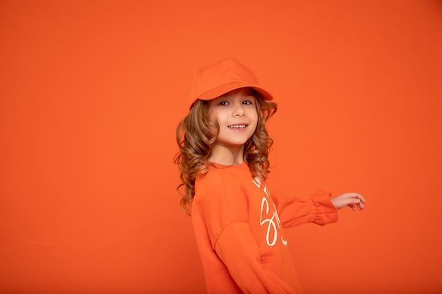 Красивая девочка 6-7 лет в оранжевой кепке с местом для текста, макет. студийная съемка, печать на текстиле, изготовление головных уборов. показываю руку
