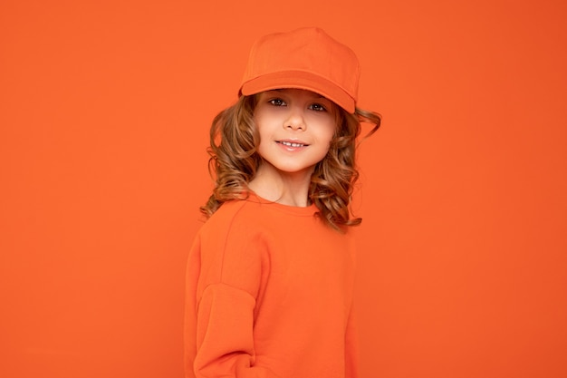Beautiful child girl 6-7 years old in orange cap with place for text, mock up. studio shot, printing on textiles, production of hats concept