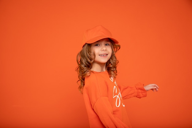 Beautiful child girl 6-7 years old in orange cap with place for text, mock up. studio shot, printing on textiles, production of hats. showing hand