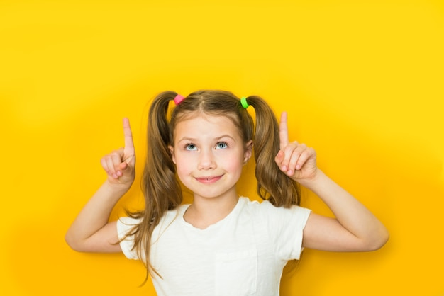 Beautiful child girl points fingers up. copy space
