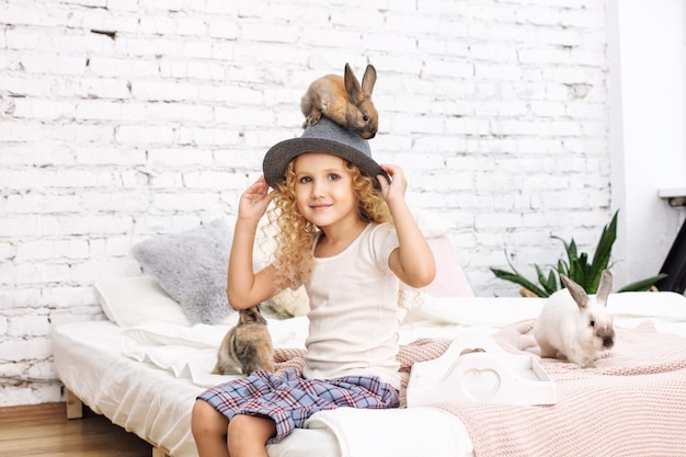 巻き毛と帽子の上に座っているふわふわのウサギの動物と美しい子供の女の子
