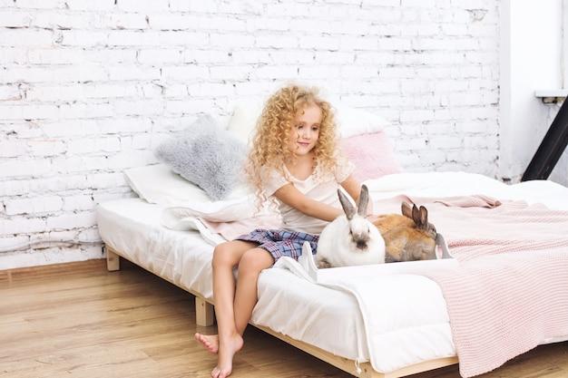 巻き毛と白いインテリアで家でふわふわのウサギの動物と美しい子供の女の子
