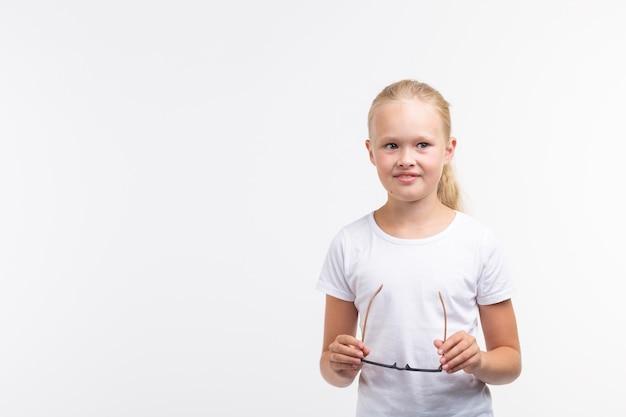 Красивая детская девочка в очках на белом фоне с копией пространства