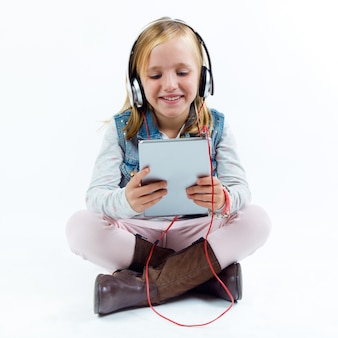 Beautiful child listening to music with digital tablet.