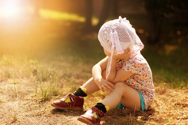 A beautiful child in the warm sunshine sits on the ground