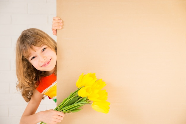 Красивый ребенок с букетом цветов прячется за баннер пустой семейный праздник день матери
