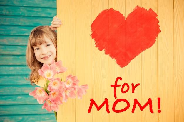 Красивый ребенок с букетом цветов, скрывающийся за деревянным фоном концепция дня матери