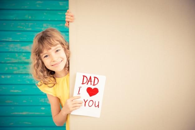 Красивый ребенок с подарочной картой за баннером пустой весенний семейный праздник концепция день отца