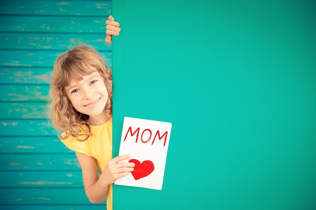Красивый ребенок с подарочной картой прячется за баннер пустой семейный праздник день матери