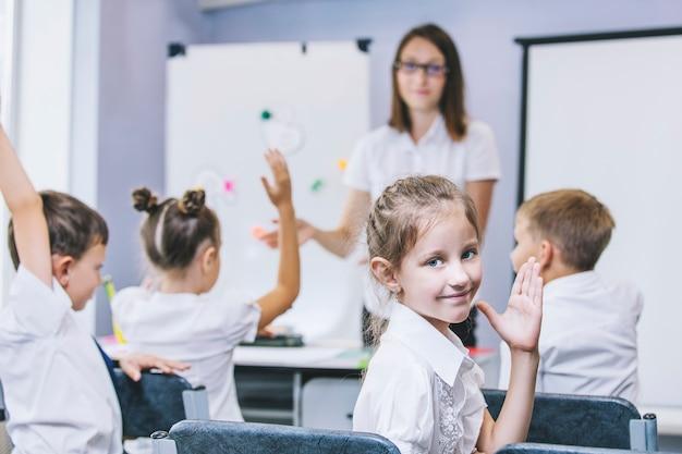 美しい子供たちは学校の教室で一緒に生徒であり、教師と一緒に教育を受けます