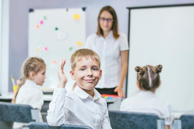 Красивые дети учатся вместе в классе в школе получают образование с учителем
