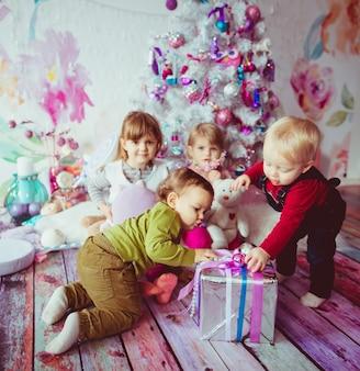 I bei bambini seduti vicino all'albero di natale