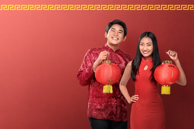 Beautiful chinese couple holding red lanterns on red background