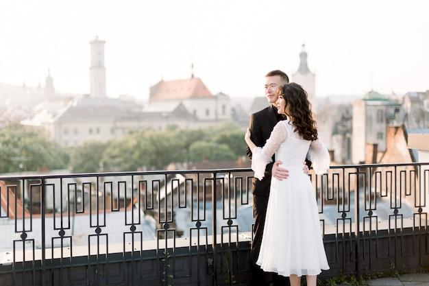 Красивая китайская свадьба пара обнимает и смотрит на восход