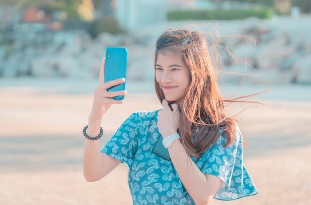 美しい中国の女性は、夏のビーチでselfieを取っています。