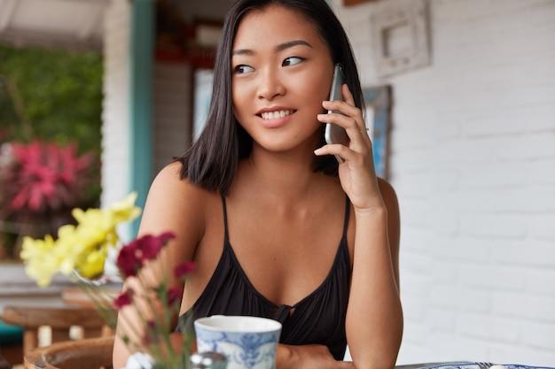 Портрет красивой китаянки разговаривает со смартфоном в кафе