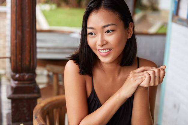 Портрет красивой китаянки с короткой прической, позирует в уютной комнате