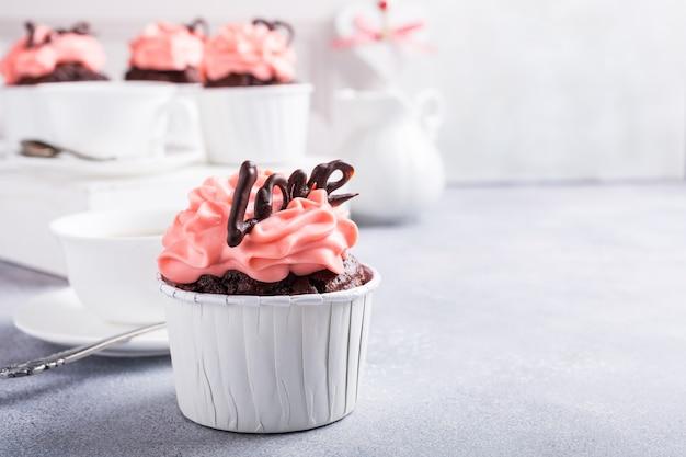 灰色の石の表面に美しいチョコレートカップケーキ、ピンクのクリームとハート。バレンタイン、母の日、コピースペースと結婚式のコンセプト