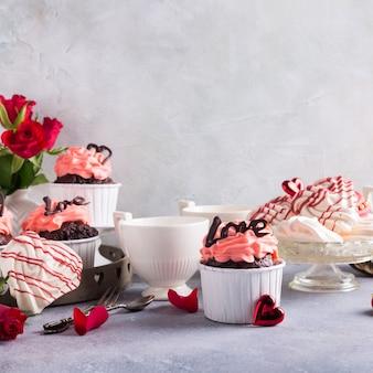 美しいチョコレートカップケーキ、ピンククリーム、メレンゲクッキー、灰色の石の表面に赤いバラ。バレンタイン、母の日、コピースペース付きの結婚式のコンセプト