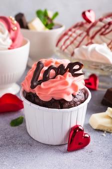 美しいチョコレートカップケーキ、ピンククリーム、メレンゲクッキー、灰色の石の表面に赤いバラ。バレンタイン、母の日、結婚式のコンセプト